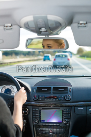 young woman drives a car on