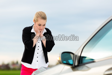 young woman with map on car