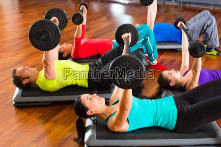 gruppe bei hanteltraining in fitnessstudio
