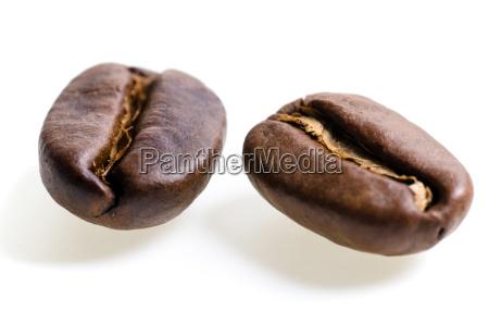 zwei espressobohnen vor weissem hintergrund