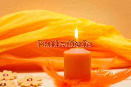 orangener hintergrund mit brennender kerze