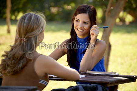 young college students talking and studying