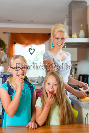 family mother makes breakfast for