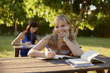 young women studying with textbook for