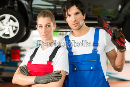 auto mechanic couple stands in garage