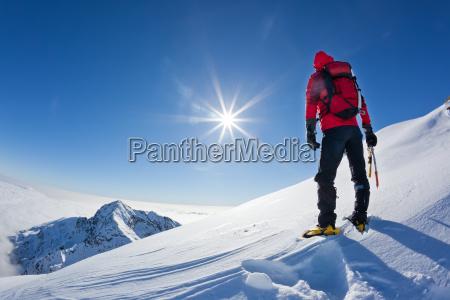 bergsteiger erreicht die spitze eines schneebedeckten