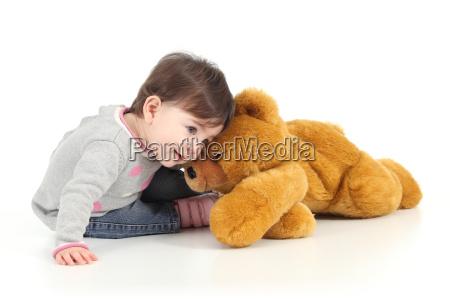 baby spielt mit einem teddybaeren