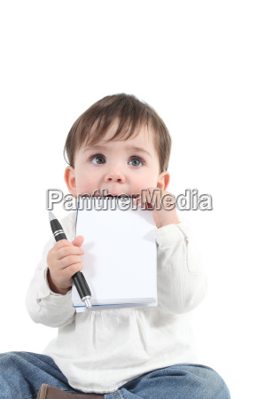 baby biting a blank notebook