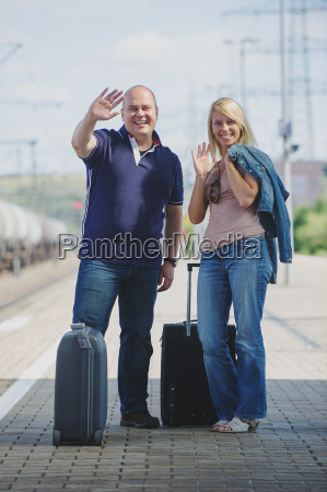 couple with suitcases on the platform