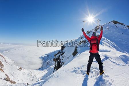 bergsteiger auf dem gipfel eines schneebedeckten