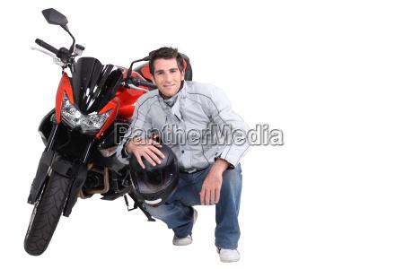 mann hockend neben motorrad