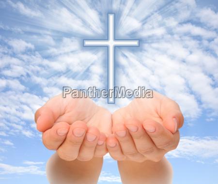haende halten christliches kreuz mit lichtstrahlen