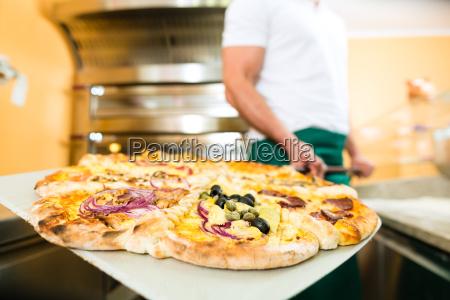 mann schiebt die fertige pizza aus