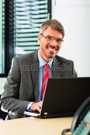 geschaeftsmann mit laptop in seinem buero