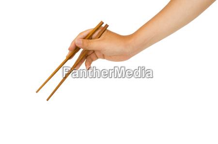 hand haelt essstaebchen