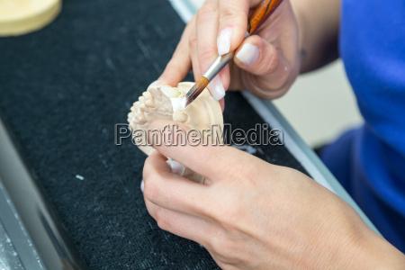 zahntechnikerin traegt keramik auf zahnersatz auf
