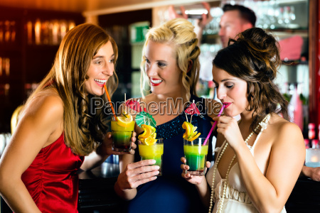 women with cocktails in club or
