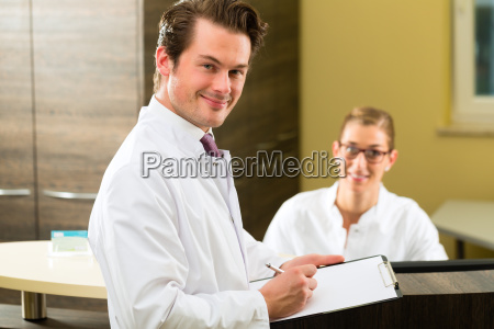 dentist with clipboard in his practice