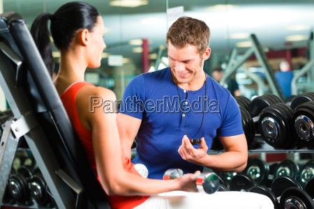 trainer und frau im fitnessstudio mit