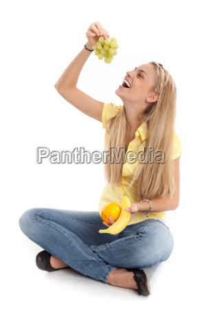 young woman eats grapes