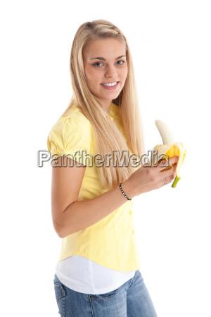 young woman eats a banana