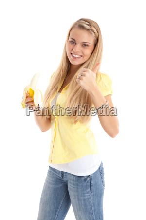 woman with banana gives thumbs up