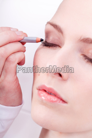 junge bruenette frau wird im kosmetikstudio