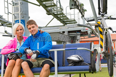 young couple sitting chair lift waiting
