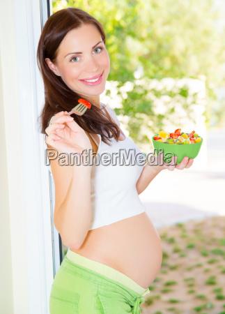 glueckliche schwangere frau essen