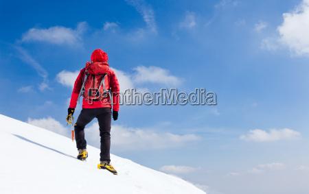 mountaineer walking uphill along a snowy