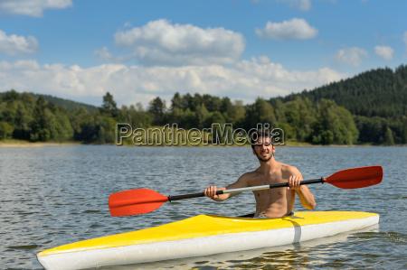 sporty man in kayak with oar
