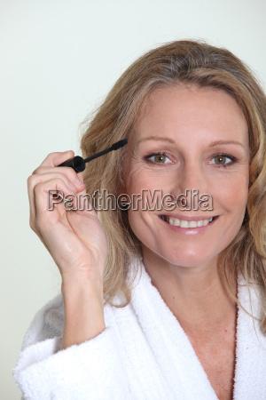 blond woman in bathrobe holding mascara