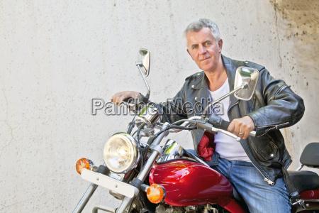 europaeischer radfahrer auf seinem motorrad entspannt