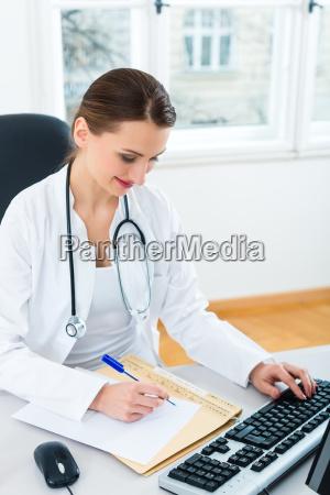 AErztin in praxis schreibt in eine