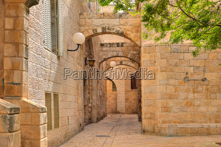 narrown cobbled street among traditional stoned