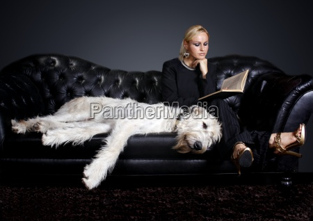 young woman with dog reading book