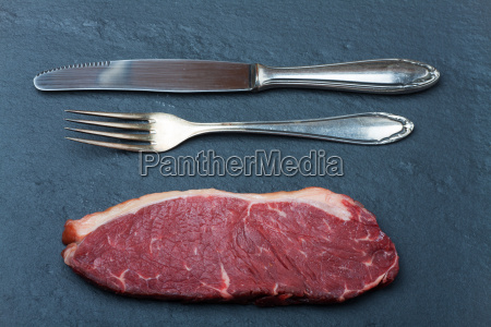 raw steak and cutlery