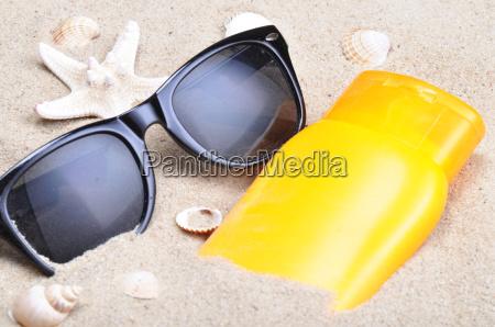 sonnenschutz und sonnenbrille auf einem strand
