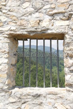 eisengitter bei fenster in natursteinmauer