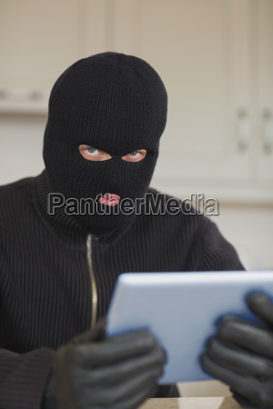 suspicious burgler holding tablet pc in