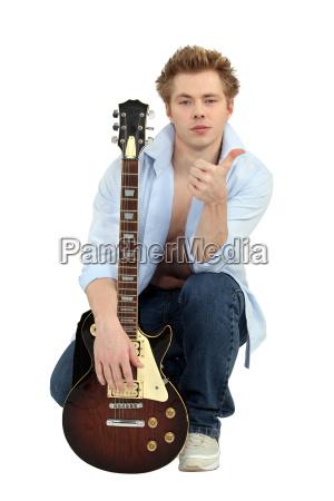 man posing with his guitar