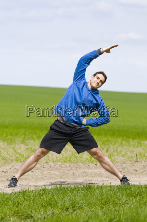 man stand and stretch the side