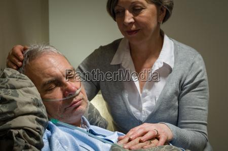 caring krankenschwester mit schlaf senior maennlichen