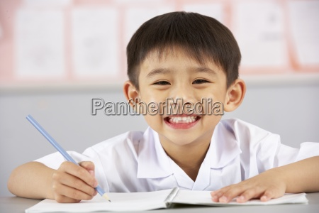 male student working at desk in