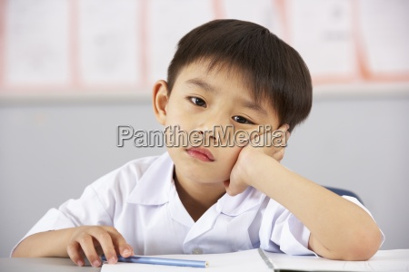 unhappy male student working at desk
