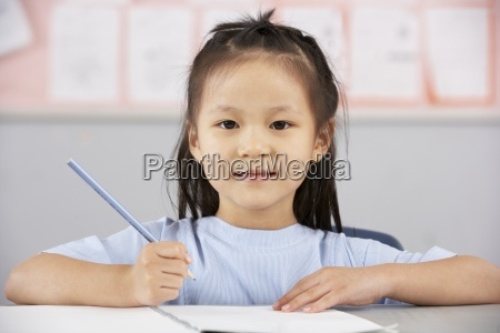 female student working at desk in