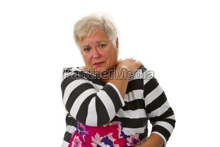seniorin mit nackenschmerzen