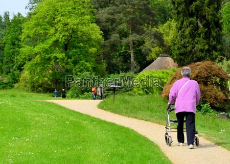 seniorin mit rollator im park