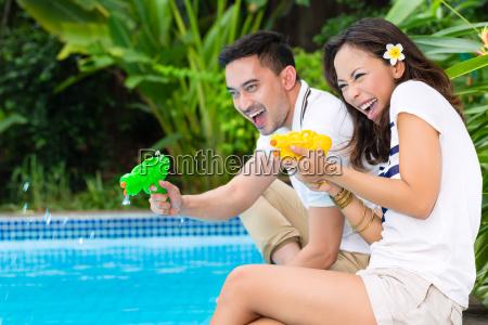 asiatisches paar draussen am pool