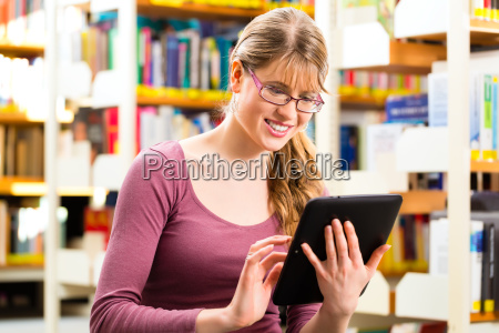 maedchen in bibliothek liest und lernt